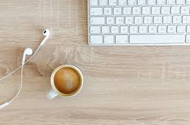 A photo looking down on a desktop with a keyboard, cup of coffee, and earphones